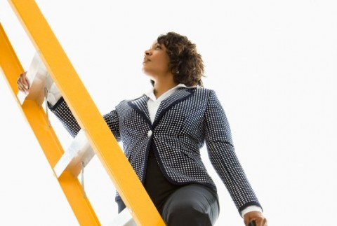 Businesswoman holding briefcase climbing ladder